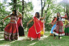 Three women in Indain dress dancing outside